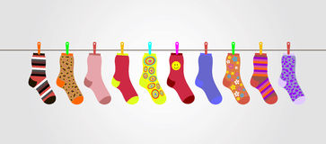 Vector colorful socks on gray background are hanging on rope Stock Images