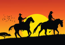 Vector cowboys. Cowboys walking on sunset Stock Image