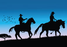 Vector cowboys. Cowboys walking on sunset. (please visit my portfolio for more Royalty Free Stock Photography