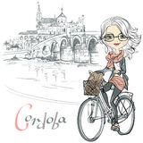 Vector cute girl rides a bicycle in Cordoba Stock Image