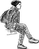 A young man sitting on a bench Stock Photo