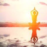 Vector el ejemplo de la silueta de la mujer de la yoga en puesta del sol del mar foto de archivo libre de regalías