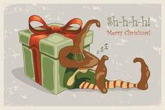 Vector el ejemplo retro de la Navidad con el duende el dormir y la caja de regalo enorme libre illustration