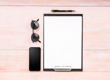 Vector el formato A4 con una pluma negra fina, un smartphone negro grande, vidrios en una tabla de madera marrón clara Imagen de archivo