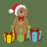 Vector el oso de peluche de la historieta en el casquillo de Papá Noel con las cajas de regalo libre illustration