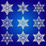 Vector el sistema del extracto de los copos de nieve blancos en azul Fotos de archivo libres de regalías