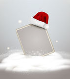 Vector festive background for the New Year and Christmas. With a sign blank standing in the snow and a red cap of Santa Claus Stock Photos
