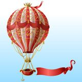 Vector flying hot air balloon with vintage decor. Vector realistic hot air balloon with vintage decor, crown, flying on blue sky with blank red ribbon for vector illustration