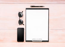 Vector A4 format with a thin black pen, a big black smartphone, glasses on a light brown wooden table. Stock Image