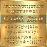 Vector gold coated alphabet letters, digits and punctuation on golden background Stock Images
