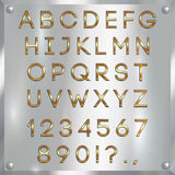 Vector gold coated alphabet letters, digits and punctuation on silver background Royalty Free Stock Image