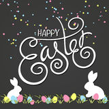 Vector hand drawn easter lettering greeting quote with swirl, curl, rabbits and colored eggs on grass. Drawing on Royalty Free Stock Image