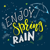 Vector hand drawn lettering quote - enjoy spring rain. With decorative branches, flowers drops and open umbrella Royalty Free Stock Image