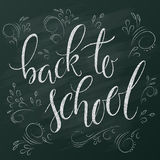 Vector hand lettering greeting text - back to school - with hand drawn curly leaves and branches on chalkboard. Background Vector Illustration