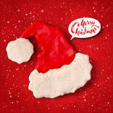 Vector plasticine figure of Santa hat. Vector hand made plasticine figure of Santa hat with shadow isolated on red festive grunge bacground with snowfall and Stock Image