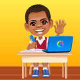 Vector happy smiling African schoolboy. Smiling happy African schoolboy in a school uniform sitting at a school desk with laptop Stock Image