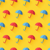 Vector icon of umbrella on yellow background. Vector vintage seamless pattern with red and blue umbrellas. Bright yellow  background. Rain protection symbol Royalty Free Stock Photos