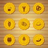 Vector icons of beer caps. Vector icons of gold beer caps with symbols attributes Oktoberfest in retro style on light wooden background Stock Image