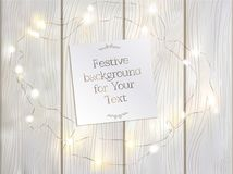 A festive light wooden background with a frame of a garland. Royalty Free Stock Photo