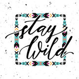 Vector illustration with hand-drawn lettering `Stay wild` and tribal frame. Trendy ethnic poster. Calligraphic design. Boho style Royalty Free Stock Images
