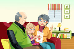 Grandparents and grandaughter reading Stock Photography