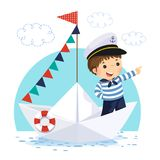 Little boy in sailor costume standing in a paper boat Royalty Free Stock Photo