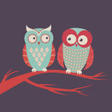 Vector illustration of two cute colorful owls. Sitting on a branch Royalty Free Stock Image
