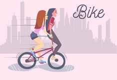 Vector illustration of two cute fashionable girls riding bike Royalty Free Stock Photography
