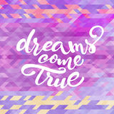 Vector inspirational quote 'Dreams come true'. For poster or card design on abstract triagle violet pattern Royalty Free Stock Image