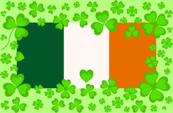 Vector Irish flag with green clover leaves around Stock Image