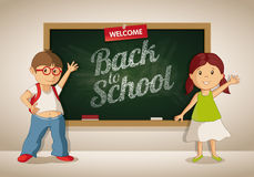 Vector little boy and girl at the blackboard in the classroom. Students are showing Welcome Back to School text on the blackboard Stock Photography