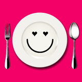 Vector of love face draw on white plate. With spoon and fork on pink background Royalty Free Stock Photography