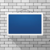 Vector mockup. Simple blue sign hanging on a gray brick wall. White rectangular frame.  Royalty Free Stock Image