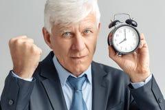 Vector moderne illustratie in vlakke stijl met de mannelijke chronometer van de handholding Zakenman die zich op grijs met wekker stock foto's