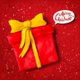 Vector plasticine figure of gift box. Vector hand made plasticine figure of gift box with shadow isolated on red festive grunge bacground with snowfall and light Royalty Free Stock Image