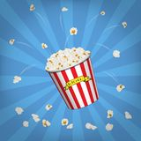 Vector Popcorn bucket with flying popcorn on blue pop art background. Popcorn bucket with flying popcorn on blue pop art background. Vector illustration Royalty Free Stock Photos