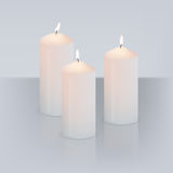 Vector realistic three candles with fire  on grey background with mirror reflection. Royalty Free Stock Photos