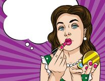 Vector retro illustration pop art comic style of a pretty woman doing makeup. Glamorous lady applying lipstick and looking at the mirror stock illustration