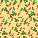 Vector seamless pattern. Candy canes and holly berry. Christmas wrapping paper design. Yellow background Stock Photo