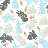 Vector seamless pattern with cute bunnies and carrots.  Stock Photos