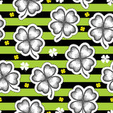 Vector seamless pattern with dotted lucky four leaf clover or shamrock in black on the striped green. Holiday background. Royalty Free Stock Image