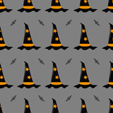 Vector seamless pattern on a Halloween theme. Witch hat and a bat on a gray background. Royalty Free Stock Photography