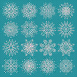 Vector set of sixteen different snowflake silhouettes on blue background. Royalty Free Stock Images