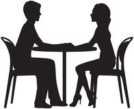 Silhouette of lovers on a date in the cafe Stock Images