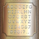 Vector silver coated alphabet letters, digits and punctuation on brass background plate Stock Photography