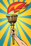 Vector torch with fire in the hand. Pop art retro style. Ancient antique Holy fire. The sports torch. Political symbol Royalty Free Stock Photography
