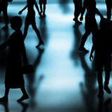 Vector walkers. Editable vector silhouettes of people walking in a crowded hall with shadows made using a gradient mesh Stock Photo
