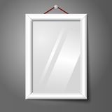 Vector white isolated vertical photo frame hanging. White isolated vertical photo frame hanging on the wall, with glass Stock Photos