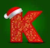 Vectoralfabetbrief K met Kerstmishoed en gouden sneeuwvlokken Royalty-vrije Stock Foto