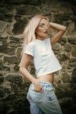 Vectoreps 10 Sexy blondevrouw die jeans dragen, die op muur stellen De jeugdstijl Royalty-vrije Stock Afbeelding
